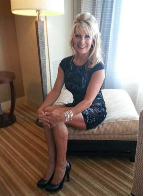 Femme mature blonde dans une chambre d'hotel en mode scort
